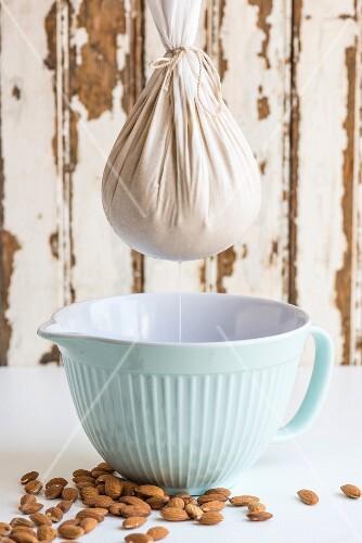 Almond milk dripping into a jug