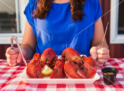 A woman holding lobster cutlery sitting in front of a platter of cooked lobster