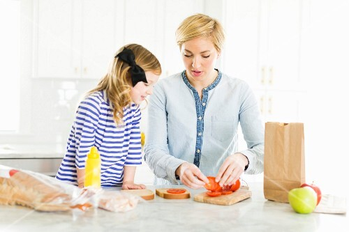 A mother and daughter in a kitchen making sandwiches