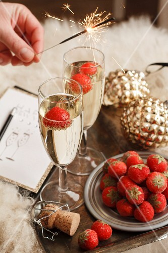A burning sparkler held over glasses of champagne with frozen strawberries