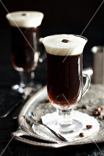 Coffee with liqueur on a silver tray with coffee beans