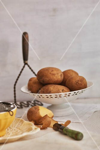 An arrangement of potatoes with a partially peeled potato and a masher