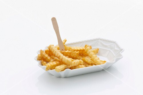 Crinkle cut chips with a wooden fork in a porcelain dish