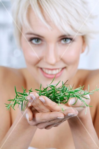 A young blonde woman holding sprigs of rosemary