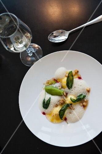 Ravioli with walnuts, foam sauce and fried basil leaves