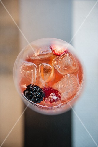 A summer drink with berries and ice cubes (seen from above)