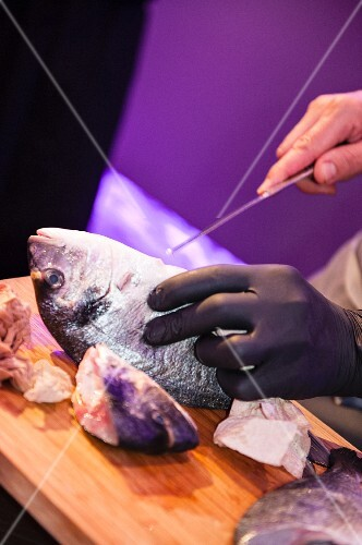 A person gutting a fish on a chopping board