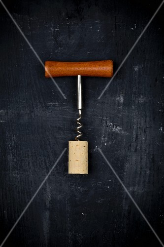 A corkscrew and a cork on a black surface