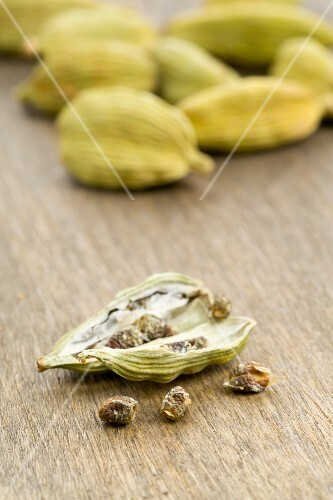 Cardamom seeds on a wooden board with cardamom pods in the background