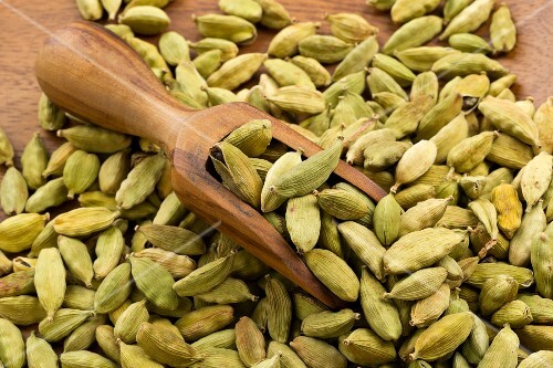 Cardamom pods in a wooden dish and on a wooden scoop