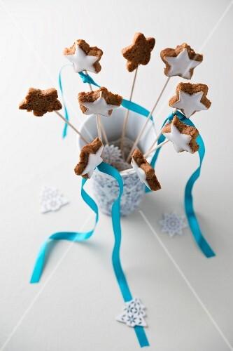 Cinnamon stars on sticks in a vase with sugar