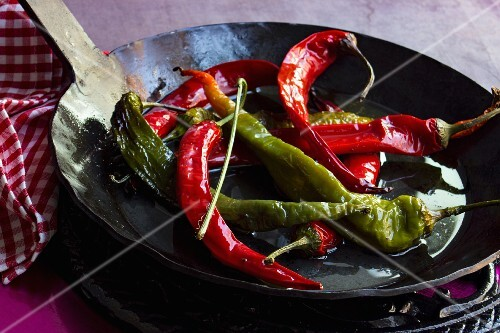 Red and green chillis fried in olive oil in a black cast-iron pan