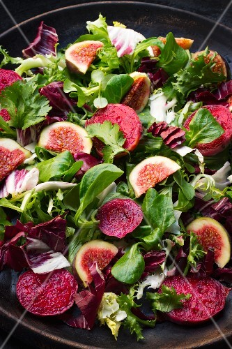 A colourful salad with prickly pears and figs on a black wooden plate