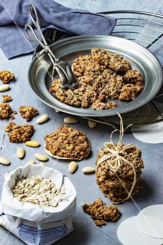 Vegan oat biscuits with almonds on a pewter plate with pastry tongs and baking ingredients