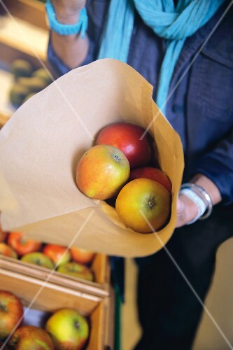 A woman holding a paper bag of organic apples