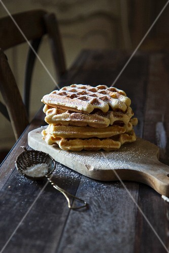 Waffles with icing sugar on a wooden board on a wooden bench