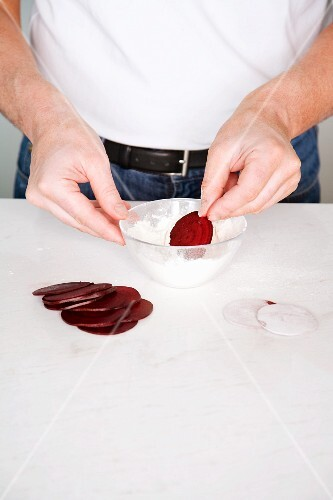 Beetroot slices being dusted with flour