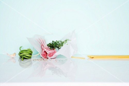 An arrangement of ingredients with lamb chops, pasta and vegetables