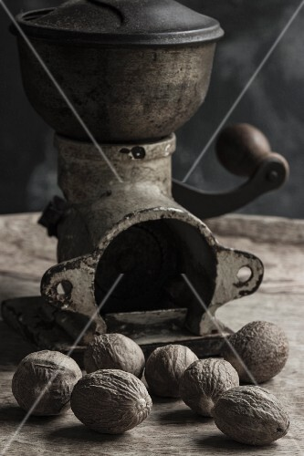 Nutmegs in front of an antique spice mill