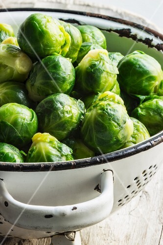 Blanched Brussels sprouts in a white metal colander