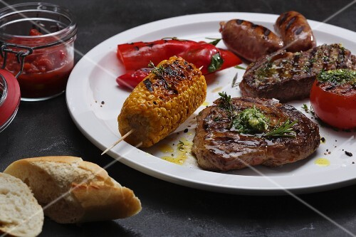 A grill platter with beef steak, sausages, a corn cob and vegetables