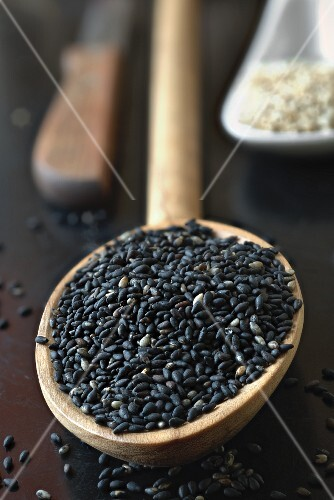 Black sesame seed in an olive wood spoon