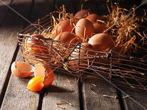 An arrangement of brown eggs in a wire basket with wooden shavings