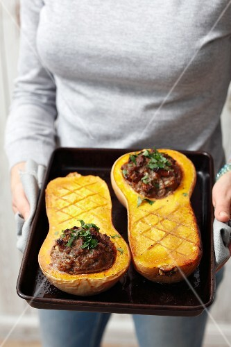 A woman with stuffed baked butternut squash