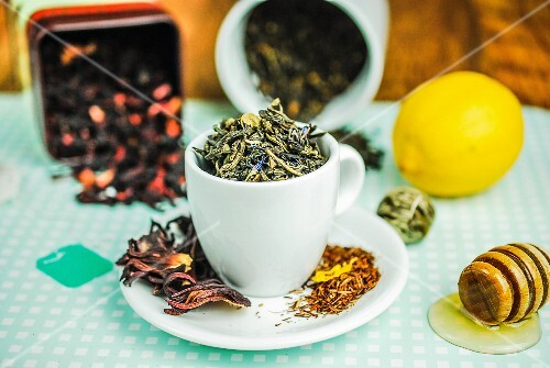 Tea leaves in a cup (green, rooibos, hibiscus) with honey and lemon