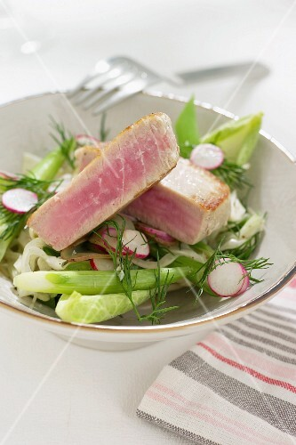 Tuna fish steak on a vegetables salad with radishes and dill