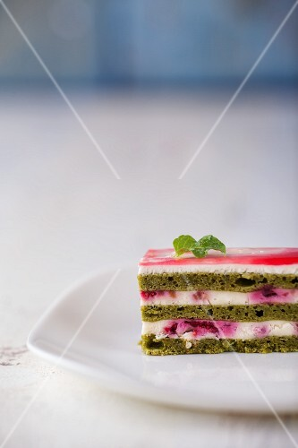 A slice of matcha cake with raspberry cream filling