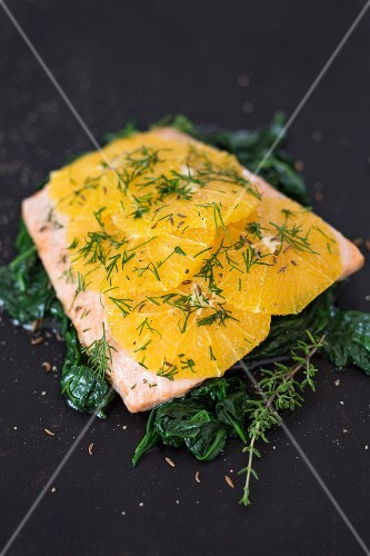 Salmon fillet with oranges and dill on a bed of spinach