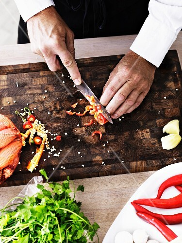 A man slicing chilli peppers into rings on a wooden board (seen from above)