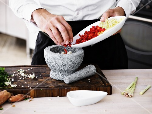 A man placing chilli and lemongrass rings into a stone mortar for crushing