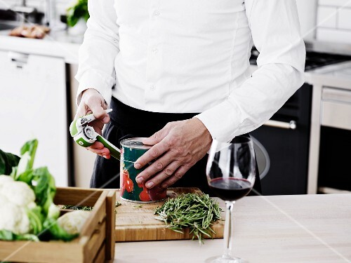 A man opening a tin in a kitchen