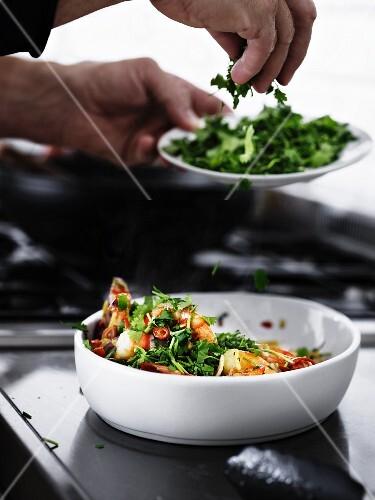 A man sprinkling chilli prawns with fresh coriander