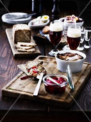 A rustic table laid with bread, pickles and beer