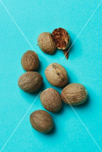 Whole nutmegs and one halved nutmeg on a blue surface