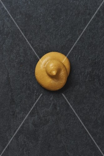 A dollop of mustard on a grey surface (seen from above)