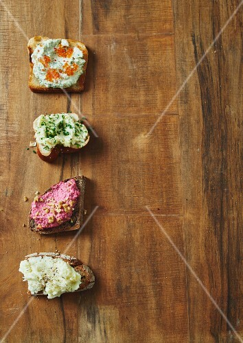 Four different spreads on slices of bread (seen from above)