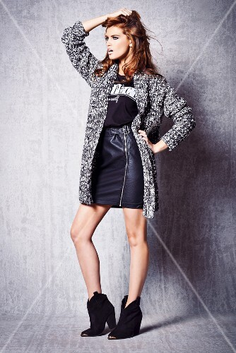 A young woman wearing a shirt, a leather skirt and a coarse-knit jacket