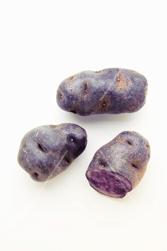 Purple potatoes on a white surface