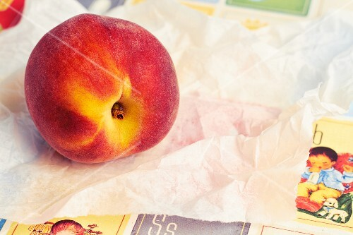 A fresh peach on a piece of white paper