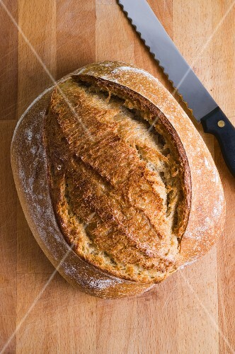 A loaf of sourdough bread on a wooden chopping board with a bread knife