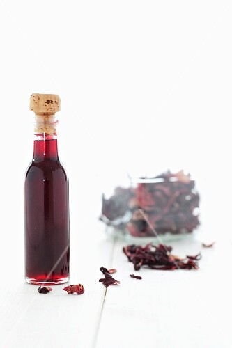 A bottle of hibiscus syrup and dried hibiscus flowers