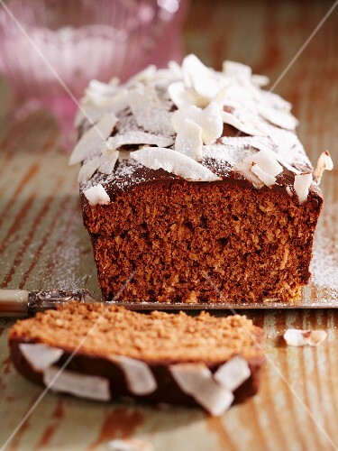 A mini coconut and chocolate cake with coconut chips, sliced