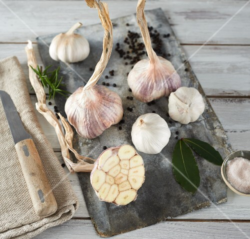 Garlic (purple and white) and bay leaves on a wooden board