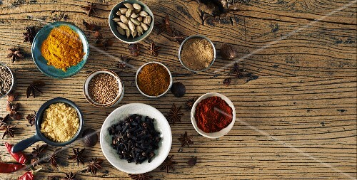 Assorted spices on a wooden surface