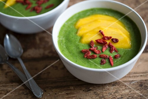 A green smoothie in a bowl with mango slices and goji berries