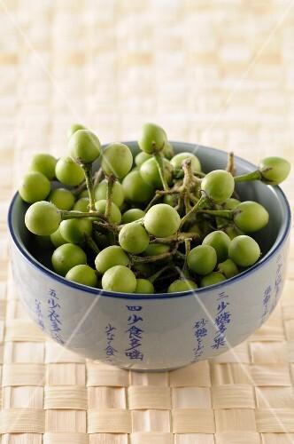 Green Thai aubergines in a ceramic bowl